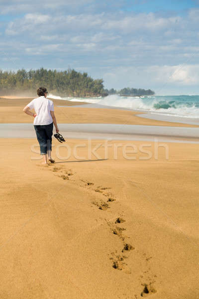 Senior woman walks on Lumahai beach in Kauai Stock photo © backyardproductions