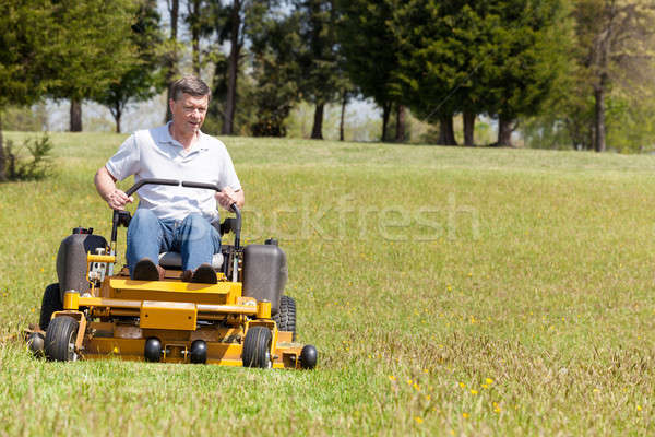 Senior man on zero turn lawn mower on turf Stock photo © backyardproductions