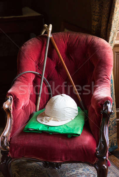 Riding silks and hat on red velvet chair Stock photo © backyardproductions