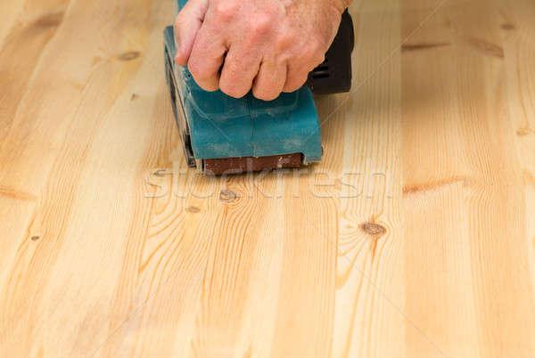 Mans hand on belt sander on pine wood Stock photo © backyardproductions