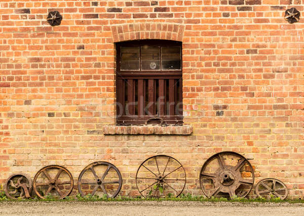 Row of old rusty cart wheels against barn Stock photo © backyardproductions