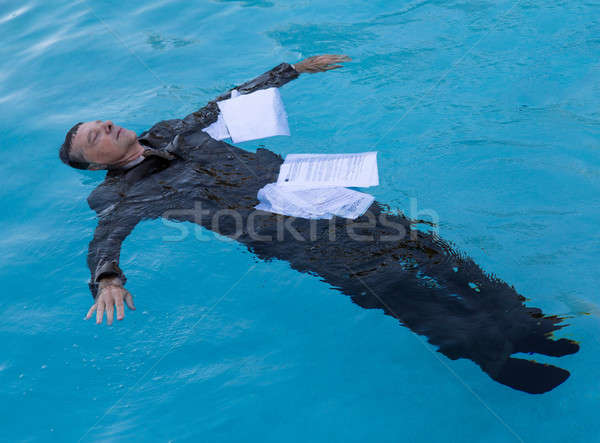Stock photo: Senior man floating among papers in water