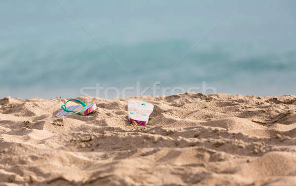 Discarded flipflops on sandy beach by ocean Stock photo © backyardproductions