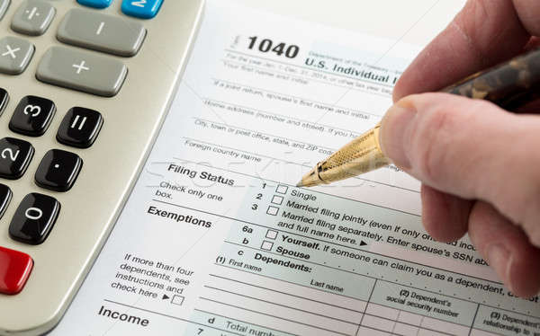 Pen and calculator on 2014 form 1040 Stock photo © backyardproductions