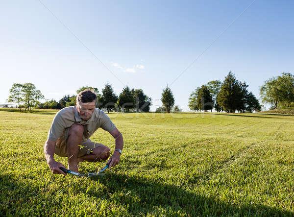 Senior man cutting grass with shears Stock photo © backyardproductions