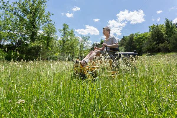Senior man on zero turn lawnmower in meadow Stock photo © backyardproductions