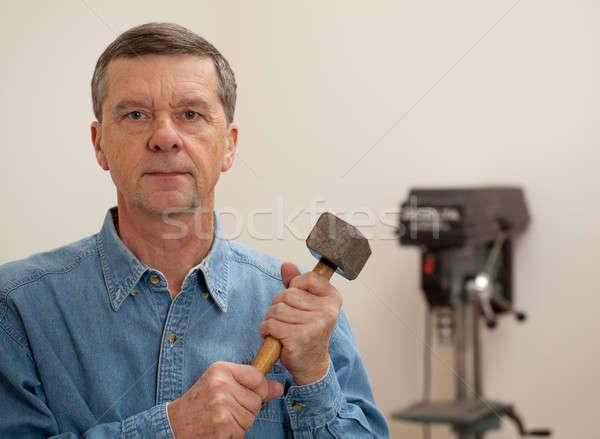 Senior man holding a large hammer Stock photo © backyardproductions