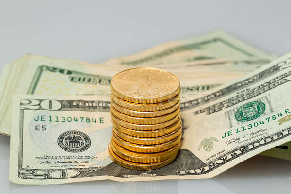 Stack of $20 dollar bills with gold coins Stock photo © backyardproductions
