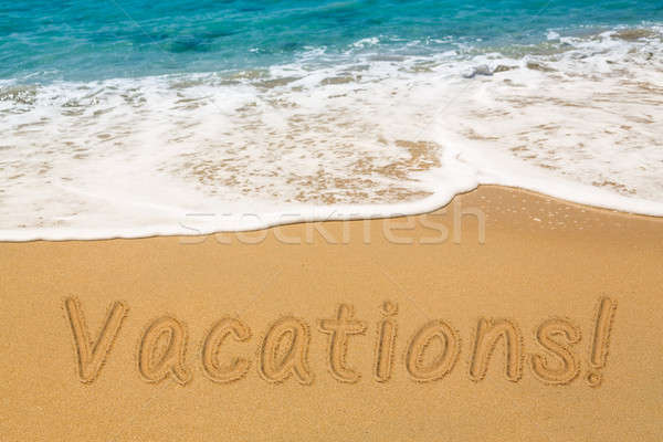 Vacations written in sand with sea surf Stock photo © backyardproductions