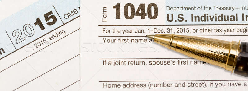 Gold pen laying on 2015 IRS form 1040 Stock photo © backyardproductions