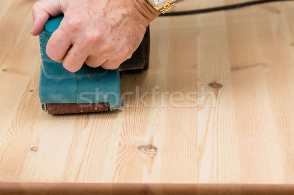 Mans hand on belt sander on pine wood Stock photo © backyardproductions