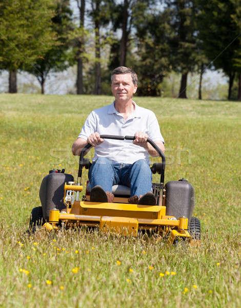 Senior man on zero turn lawn mower on turf Stock photo © backyardproductions