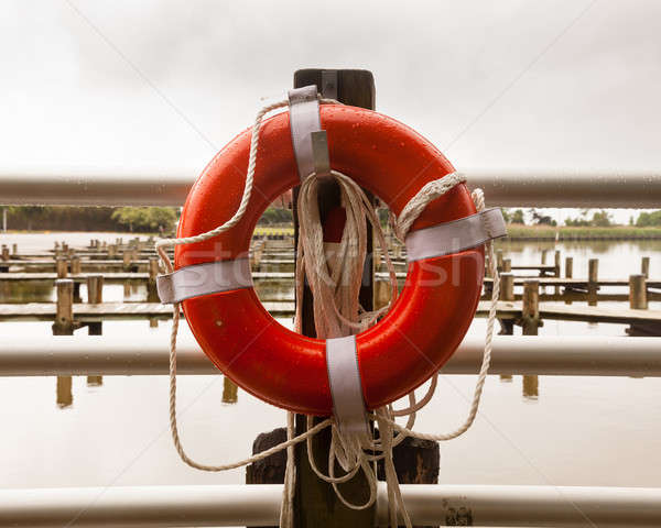 Red life belt in front of empty boat dock harbor Stock photo © backyardproductions