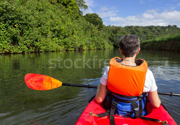 Senior lady in canoe approaching Hanalei bridge Stock photo © backyardproductions