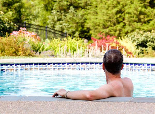 Senior man by edge of swimming pool Stock photo © backyardproductions