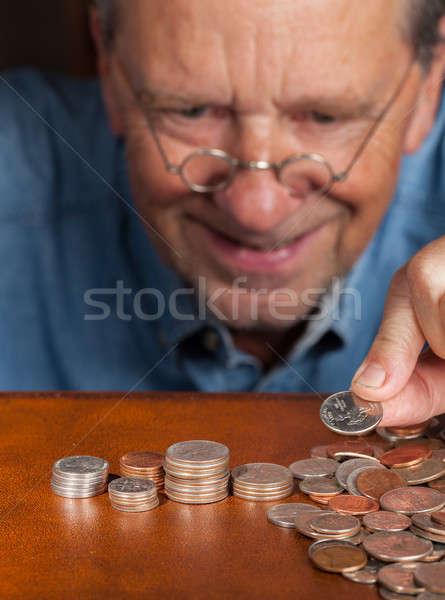 Senior man counting cash into piles Stock photo © backyardproductions