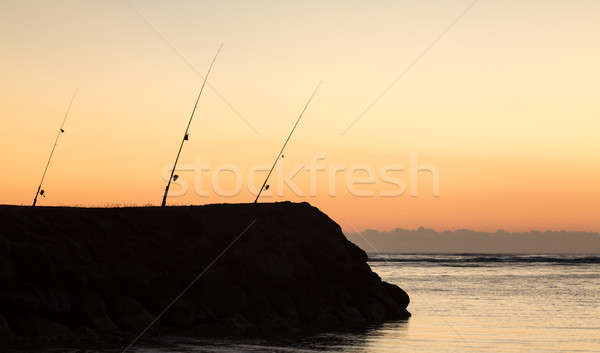 Three fishing rods at sunset over ocean Stock photo © backyardproductions