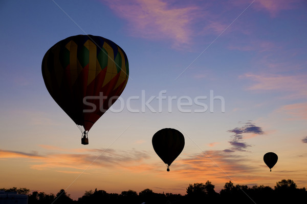 Hot-air balloons floating against a reddish dawn sky Stock photo © Balefire9