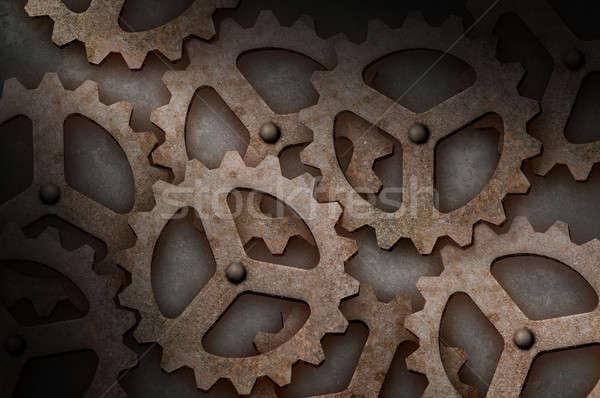 Distressed interlocking gears lit diagonally Stock photo © Balefire9
