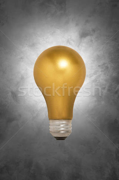 Gold Light Bulb Floating Against a Gray Background Stock photo © Balefire9