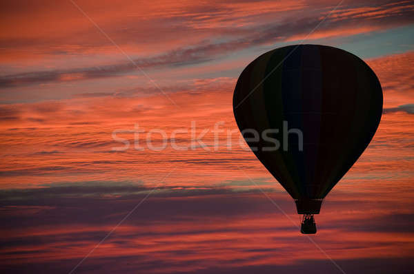 Hot-air ballooning among pink and orange clouds  Stock photo © Balefire9