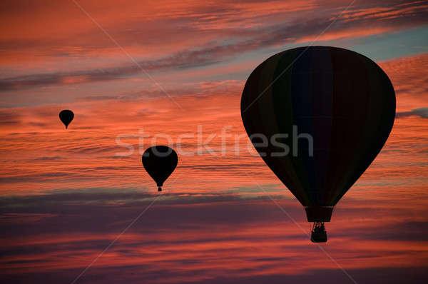 Hot-air balloons floating among clouds at dawn Stock photo © Balefire9