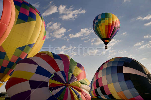 Stock photo: Hot air balloon floating over other inflating balloons
