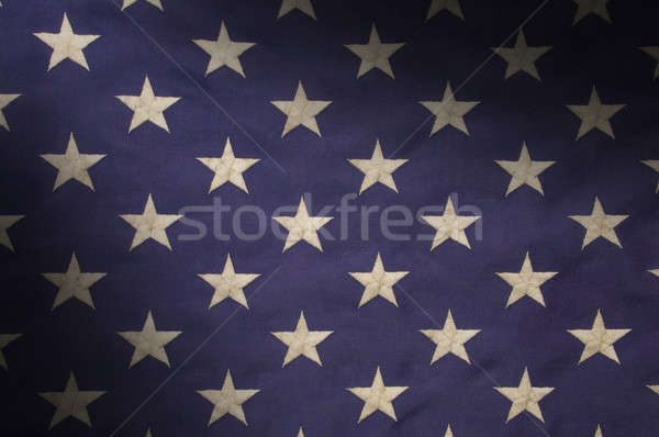Stock photo: Stars in a field of blue on an American flag lit diagonally