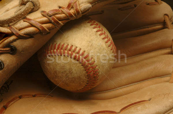 Well-used baseball nestled in a glove. Stock photo © Balefire9