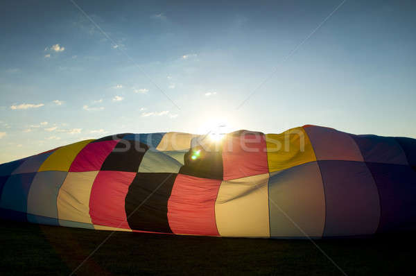 Sun peaking over the inflating envelope of a hot air balloon Stock photo © Balefire9
