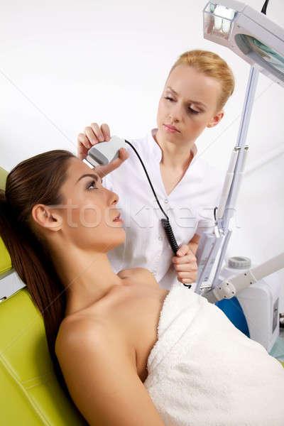 woman having a stimulating facial treatment from a therapist Stock photo © bartekwardziak