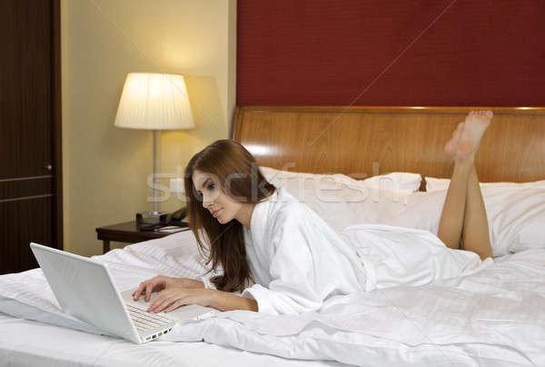 ブルネット 女性 見える ノートパソコン ベッド ホーム ストックフォト © bartekwardziak