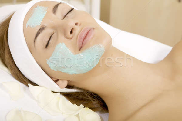 young woman getting beauty skin mask treatment on her face with  Stock photo © bartekwardziak