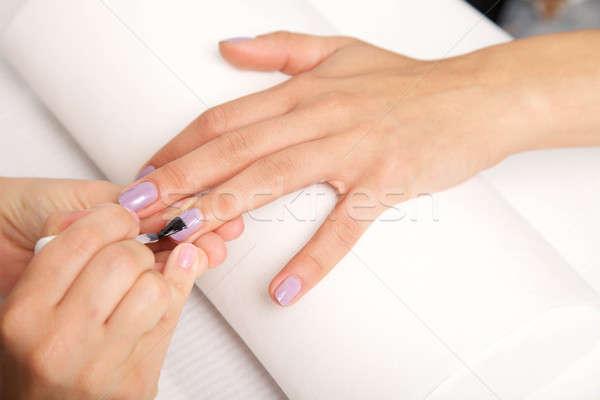 Manicure - Beautiful manicured woman's nails with violet nail po Stock photo © bartekwardziak