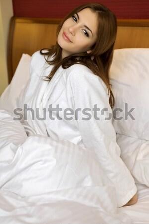 beautyful brunette woman lying in bedroom smiling on a white bac Stock photo © bartekwardziak