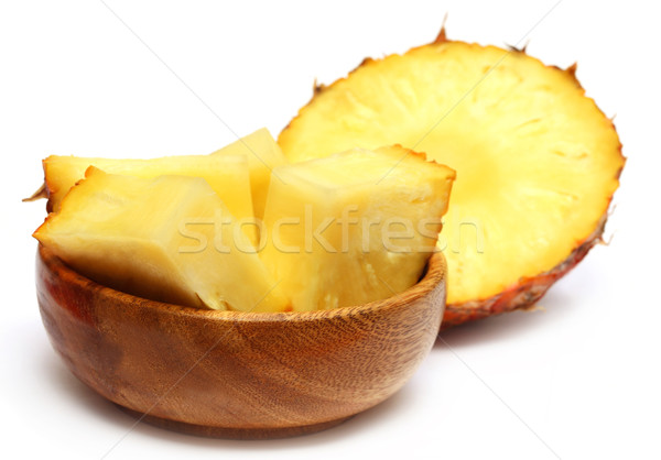 Sliced pineapple on a wooden bowl Stock photo © bdspn