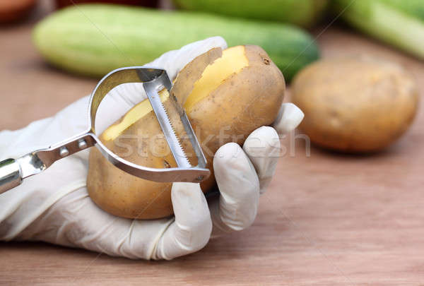 Peeling potato in kitchen Stock photo © bdspn