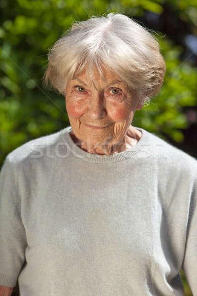Amavelmente idoso senhora em pé jardim olhando Foto stock © belahoche