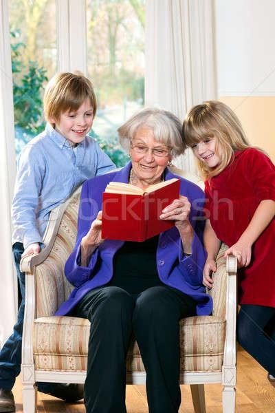 Grootmoeder lezing kleinkinderen twee cute jonge Stockfoto © belahoche