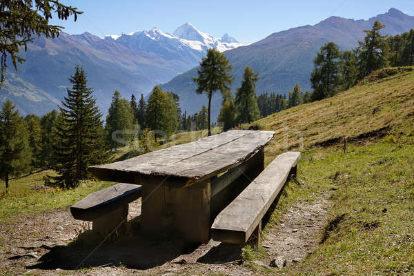 Empty rustic picnic table and benches on a slope in the mountains, Alps. Stock photo © belahoche
