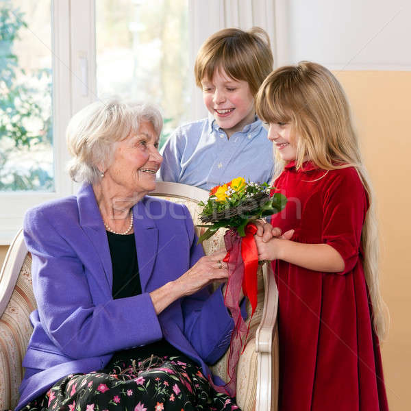 Stock photo: Children giving grandmother flowers