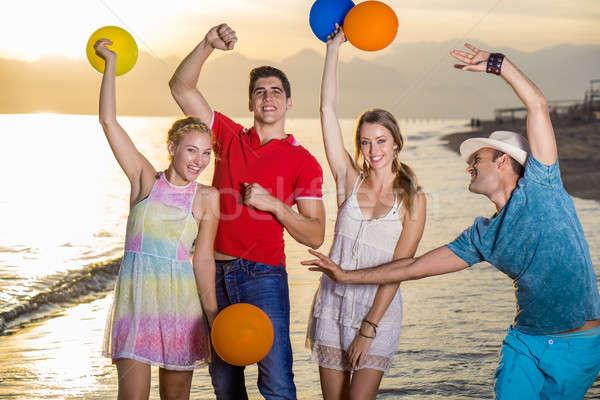 Gelukkig vrienden strand ballonnen jonge genieten Stockfoto © belahoche