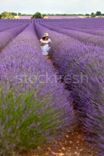 Pretty girl in white dress sitting in floral field of lavender,  Stock photo © belahoche