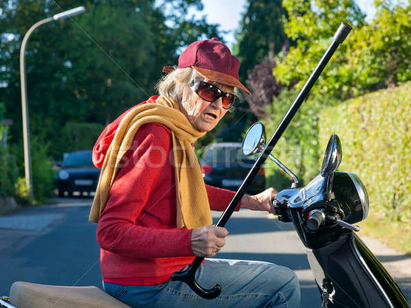 Stock photo: Senior lady on a scooter waving her cane