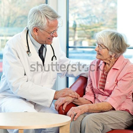 Doctor taking an elderly womans blood pressure Stock photo © belahoche
