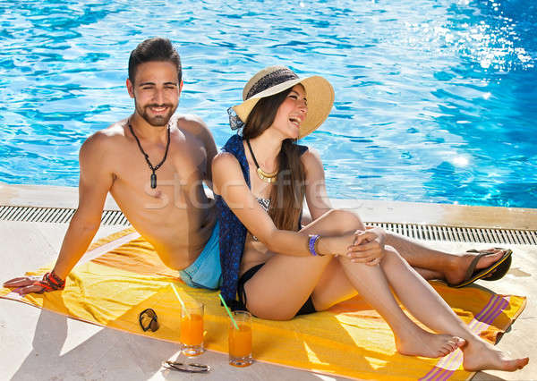 Happy carefree couple relaxing poolside Stock photo © belahoche