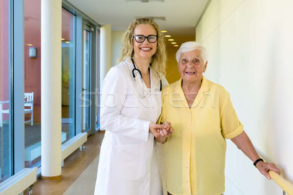 Kind Nurse Assisting Old Patient at the Hallway Stock photo © belahoche