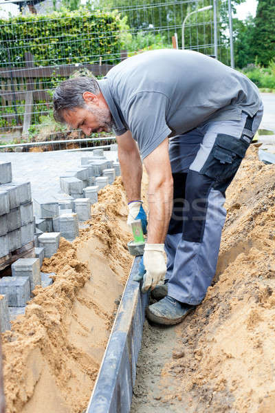 Construction worker place border stones. Stock photo © belahoche