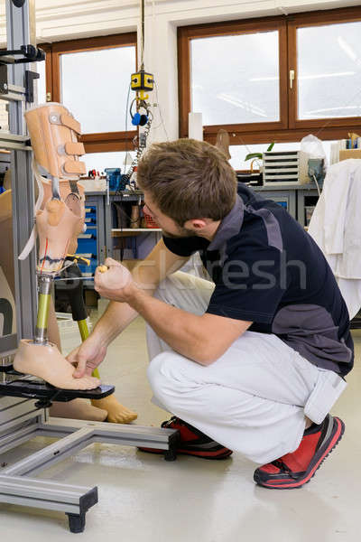 Technician working on prosthetic leg parts Stock photo © belahoche