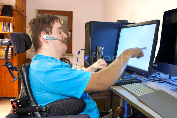 Man with infantile cerebral palsy using a computer Stock photo © belahoche